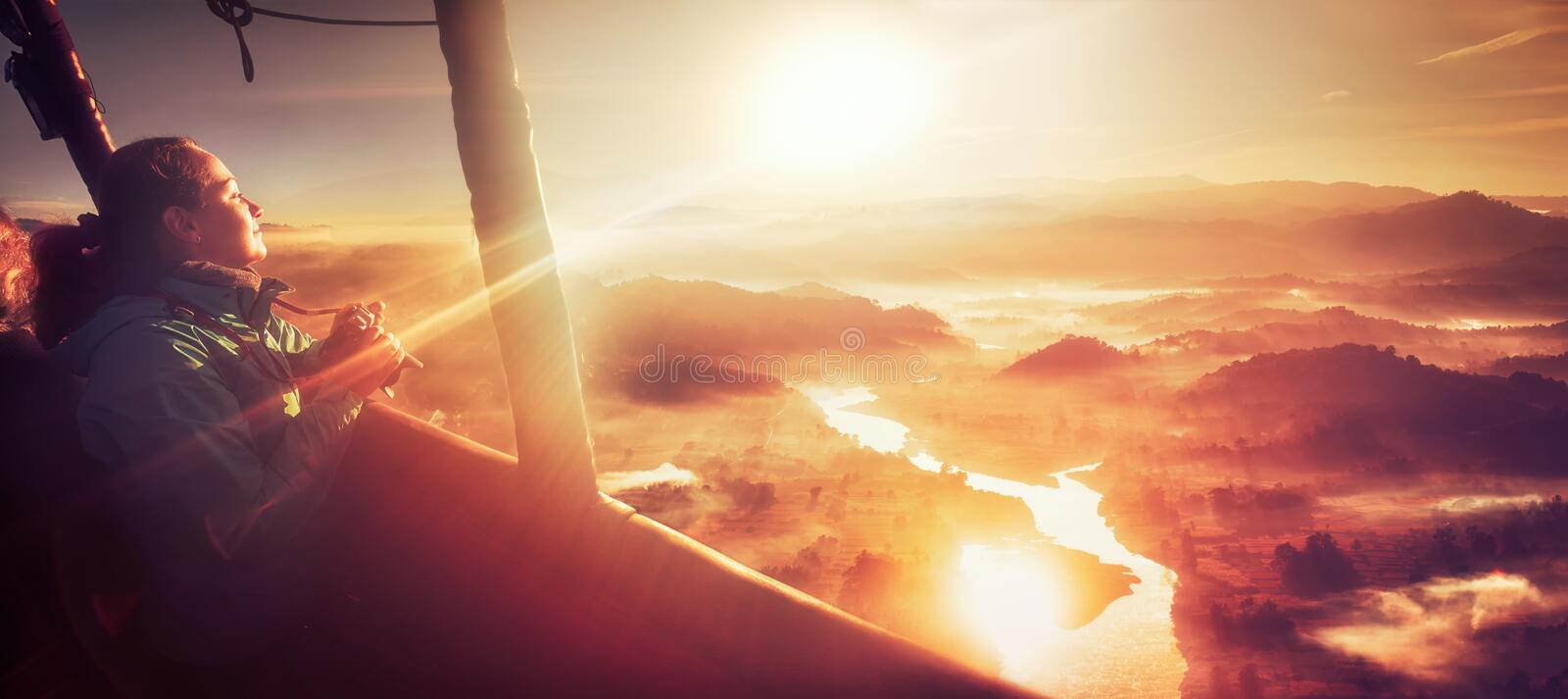 Happy woman traveling by hot air balloon. Happy young woman traveling by balloon during Sunrise over the fairytale landscape hills of near Ngapali, Myanmar royalty free stock photos
