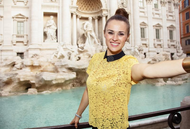 Happy woman at Trevi Fountain in Rome, Italy taking selfie. Happy young woman in yellow blouse at Trevi Fountain taking selfie royalty free stock photos