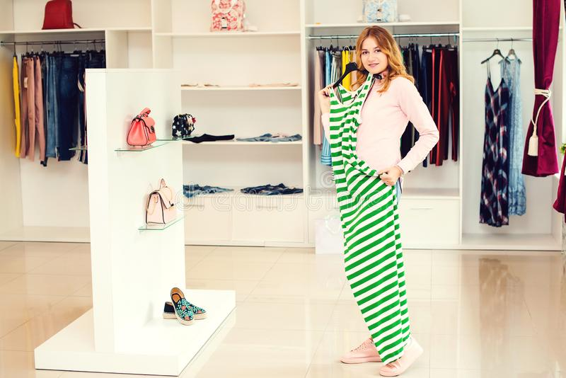 Happy woman trying on new dress in showroom. Fashion and choice concept. Shopping, fashion, clothes, style and people concept. stock image