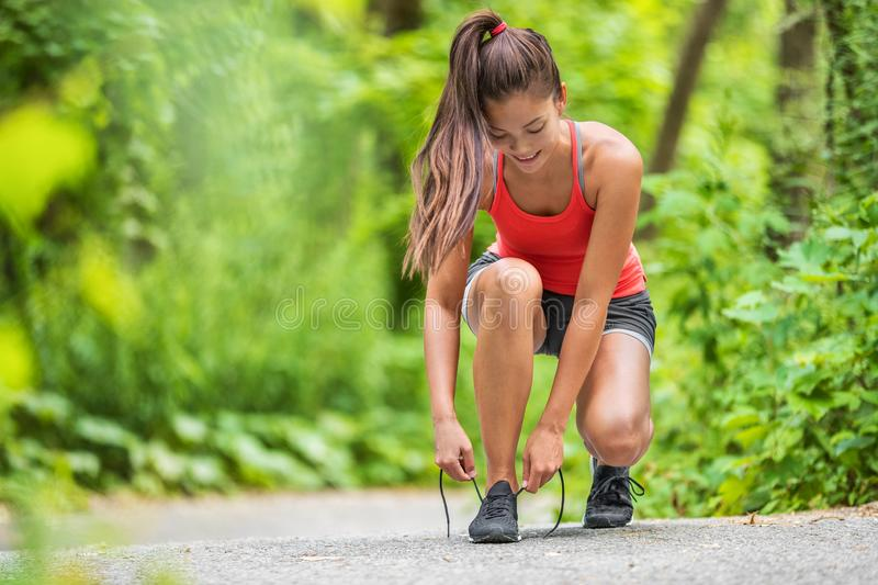 Happy woman tying running shoes getting ready to walk or run jogging in outdoor forest. Asian fit girl preparing to jog. Outside royalty free stock photography