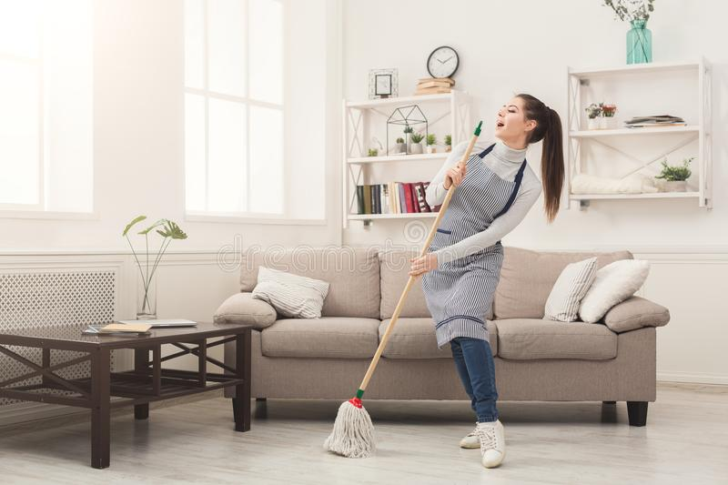 Woman in uniform cleaning home with mop and having fun. Happy woman in uniform cleaning home, singing at mop like at microphone and having fun, copy space royalty free stock image