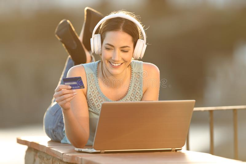 Happy woman uses credit card to buy online music or media. With a laptop in a balcony wall royalty free stock photo
