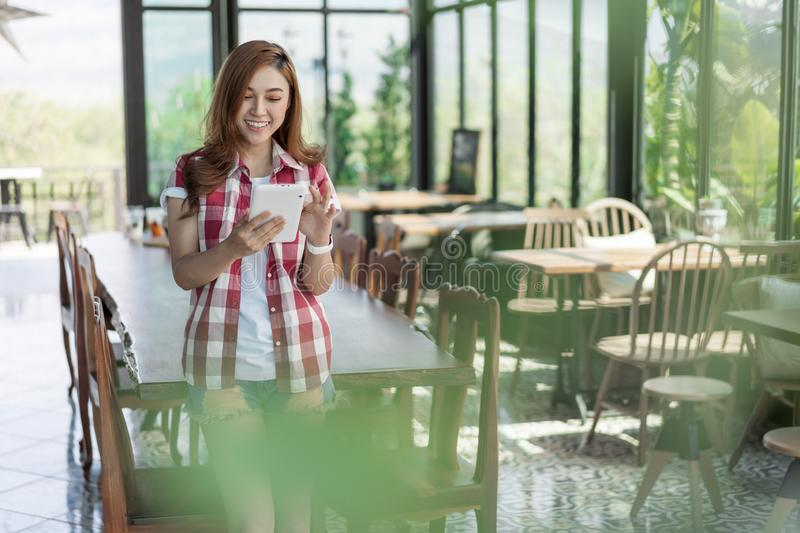 Happy woman using digital tablet in cafe. Happy woman using digital tablet in a cafe royalty free stock image