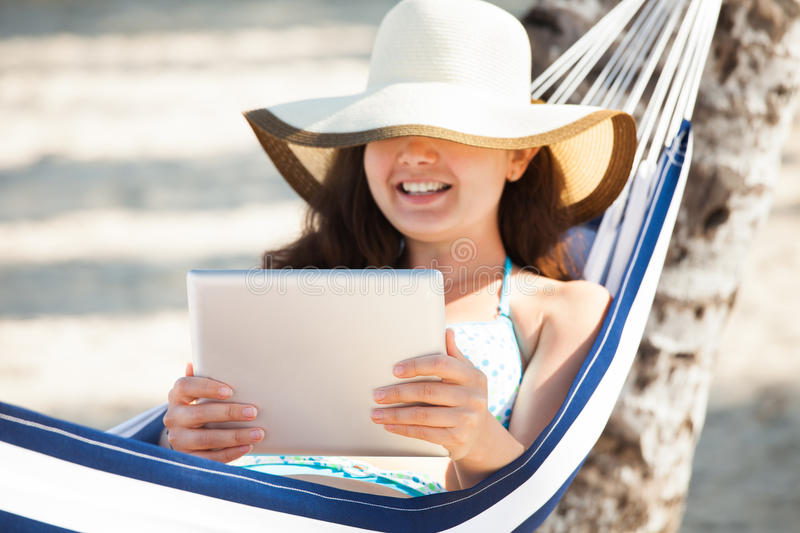 Happy Woman Using Digital Tablet In Hammock royalty free stock image