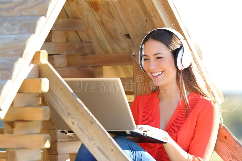 Happy woman using laptop and headphones in a wood house stock photography