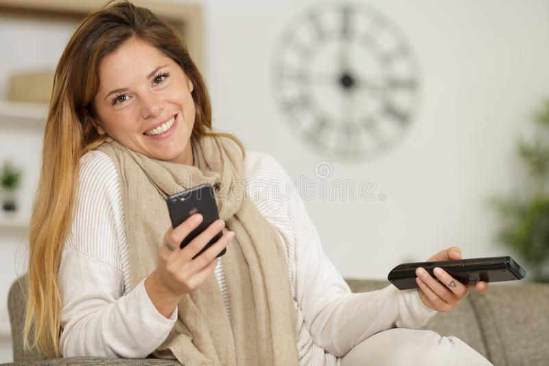 Happy woman using mobile phone on sofa stock photos