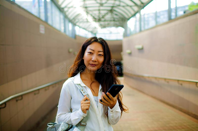 Happy woman using smart phone while standing at the transition. royalty free stock photography