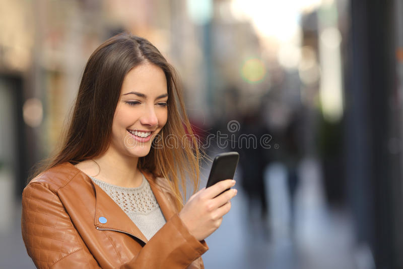 Happy woman using a smart phone in the street. With an unfocused background