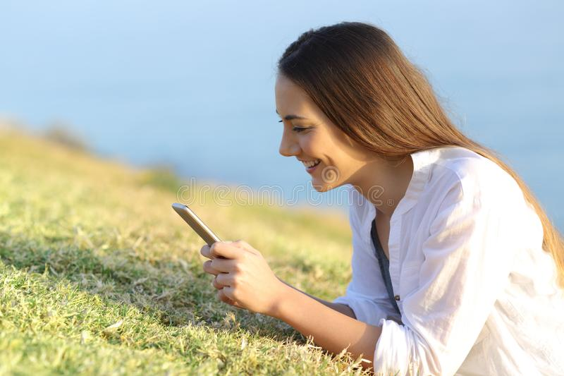 Happy woman using a smartphone lying on the grass royalty free stock image