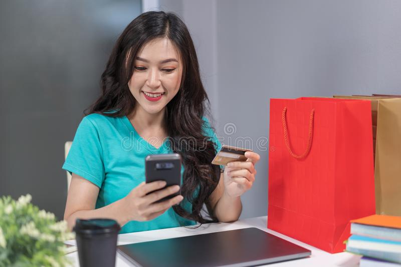 Happy woman using smartphone for online shopping with credit car stock images