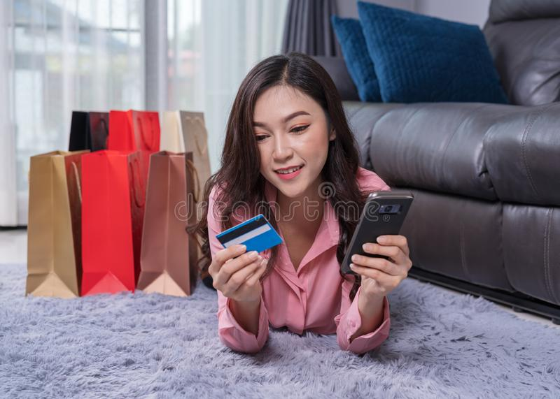 Happy woman using smartphone to shopping online with credit card. In the living room stock photography