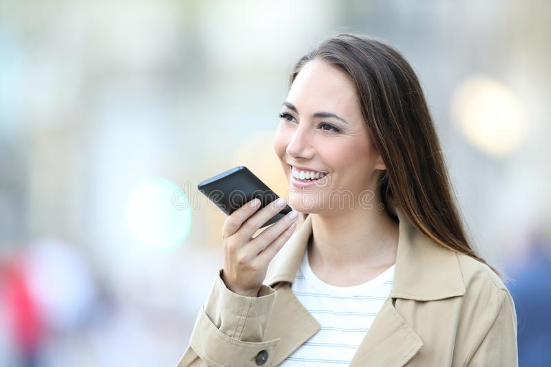 Happy woman using voice recognition on cell phone royalty free stock image