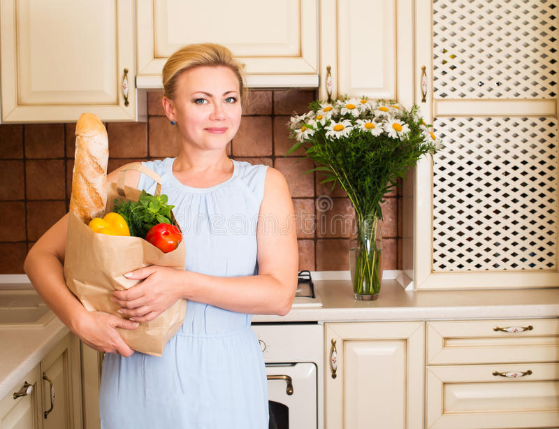 Happy woman with vegetables and bread in paper shopping bag. Beauty girl in the kitchen ready to cook healthy food. Diet concept. stock images
