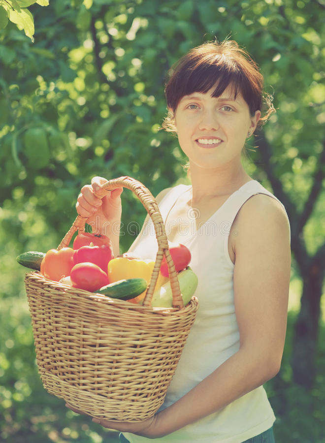 Happy woman with vegetables. Happy young woman with vegetables harvest in garden stock image