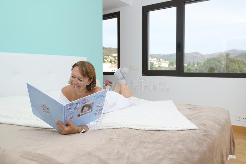 Happy woman viewing a family photo album lying face down on the bed in the bedroom in an environment corresponding to an stock photo