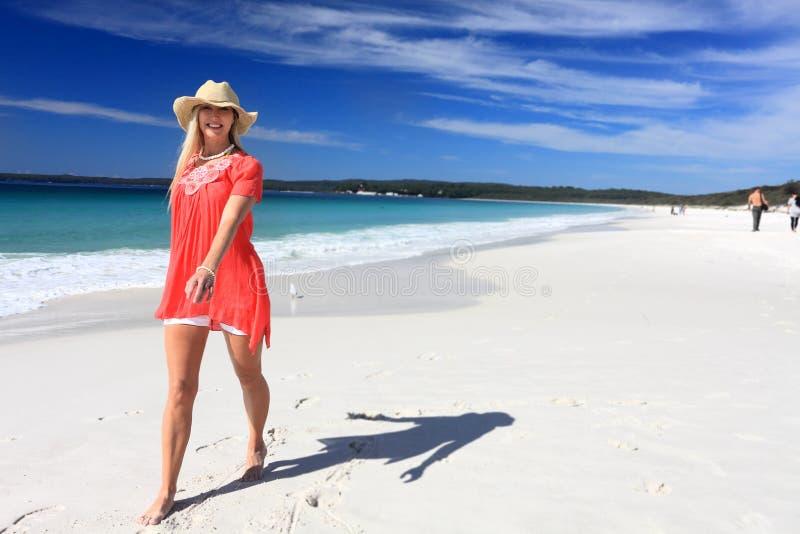 Happy woman walking along beautiful beach royalty free stock photo