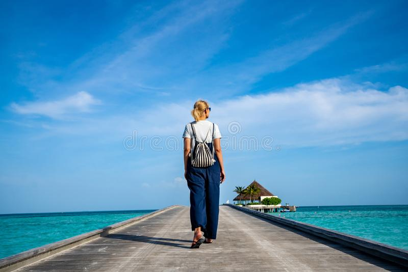 Happy woman walking along the wooden pier with blue sea and sky background royalty free stock image
