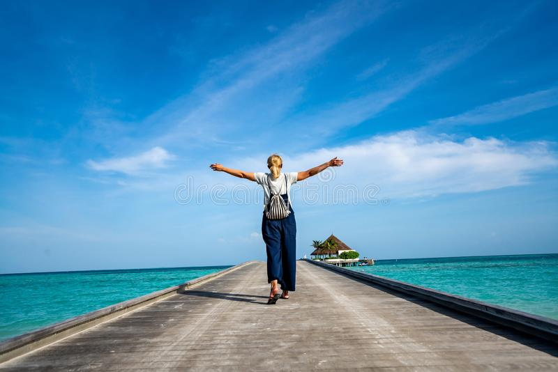 Happy woman walking along the wooden pier with blue sea and sky background.  stock photography