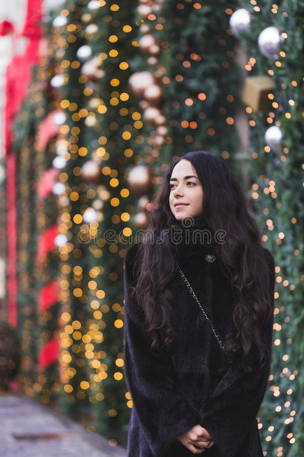 Happy woman walking in a black mink coat in city decorated for New Year stock images