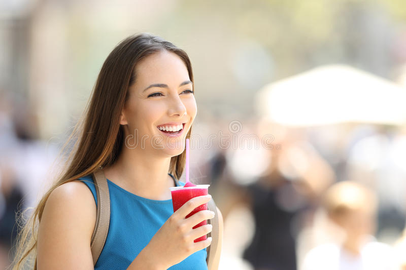 Happy woman walking and holding a slush stock images