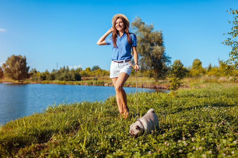 Happy woman walking with pug dog by river. Dog and woman chilling outdoors royalty free stock photography
