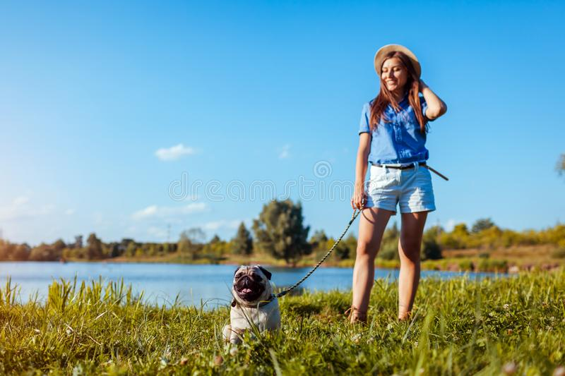 Happy woman walking with pug dog by river. Dog and woman chilling outdoors royalty free stock image