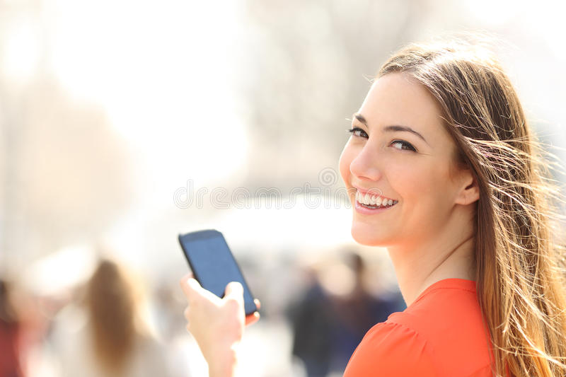 Happy woman walking in the street using a smartphone. Happy woman smiling and walking in the street using a smartphone and looking at camera royalty free stock photo