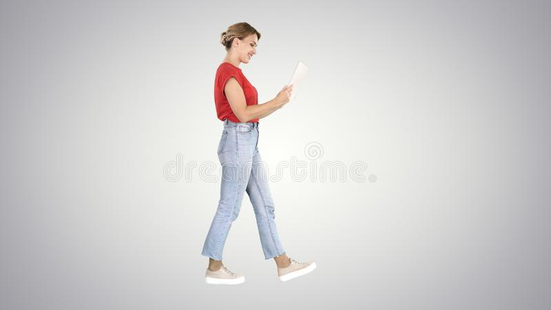 Happy woman walking with tablet on gradient background. royalty free stock photo