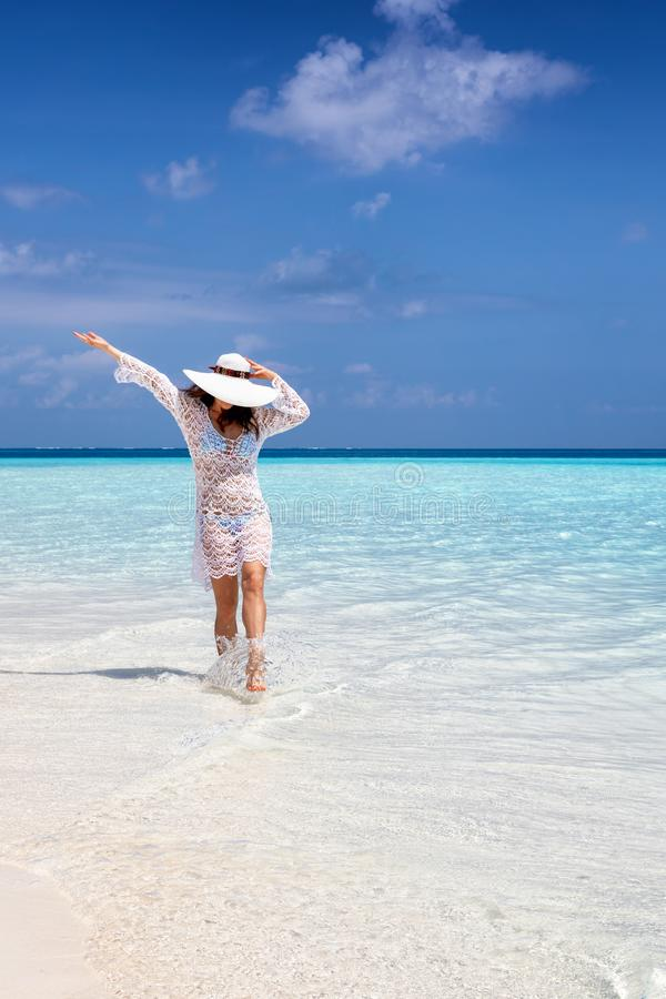 Happy woman walks on a beach with turquoise ocean royalty free stock photos
