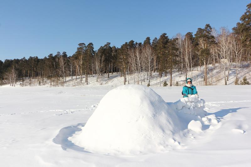 Happy woman in warm clothes standing near igloo on a snow glade in the winter, Siberia, Russia royalty free stock photos