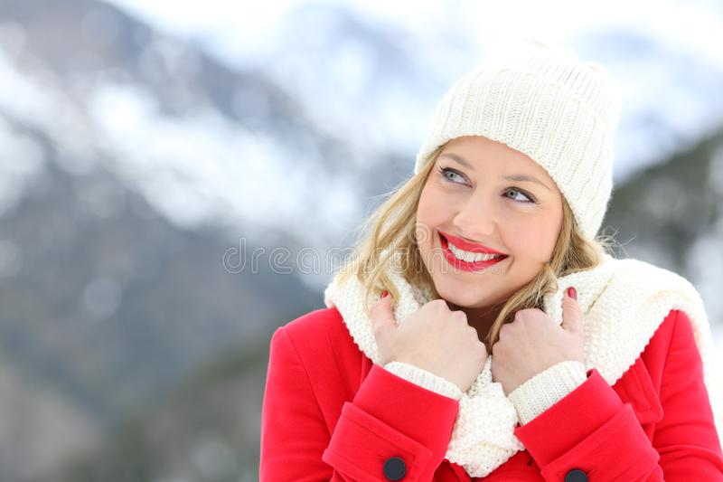 Woman warmly clothed looking at side in winter. Happy woman warmly clothed in red looking at side in winter in the mountain royalty free stock photography