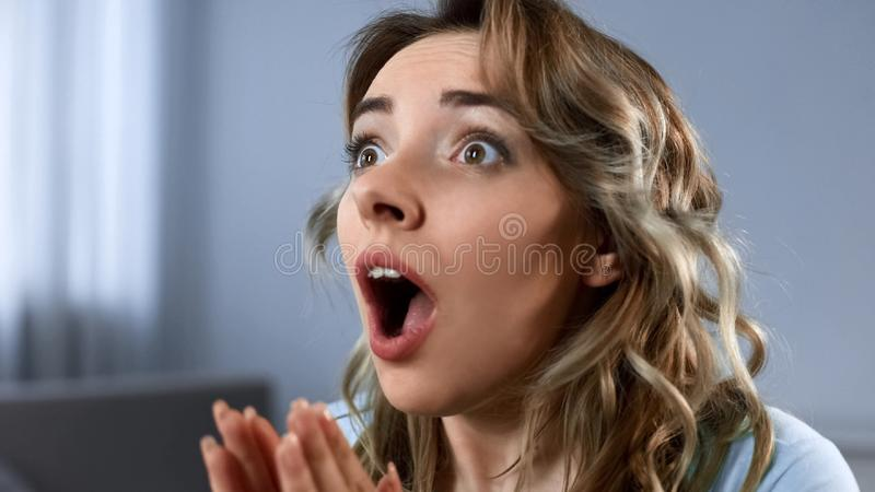 Happy woman watching football game on tv, supporting team, cheering for goal stock photography