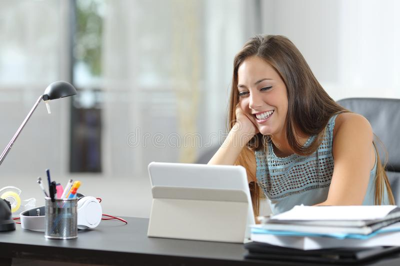 Happy woman watching tablet media on a desk at home stock photos