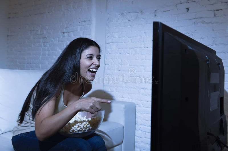 Happy woman watching television at sofa couch happy excited enjoying eating popcorn. Young beautiful latin woman home alone watching television smiling sitting stock photography