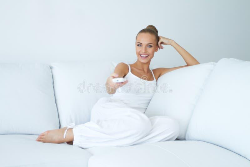 Happy woman watching tv on sofa stock photography