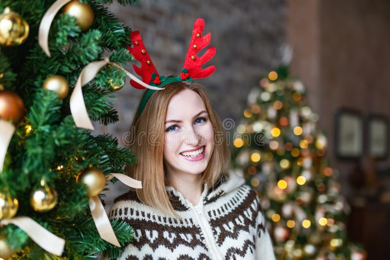 Happy woman wearing Christmas antlers of a deer near Christmas tree royalty free stock photography