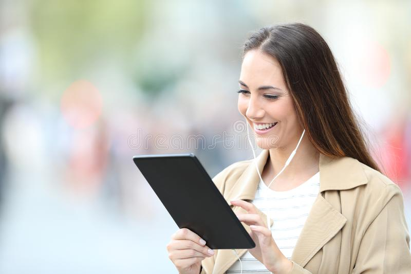 Happy woman wearing earbuds using tablet in the street stock photos