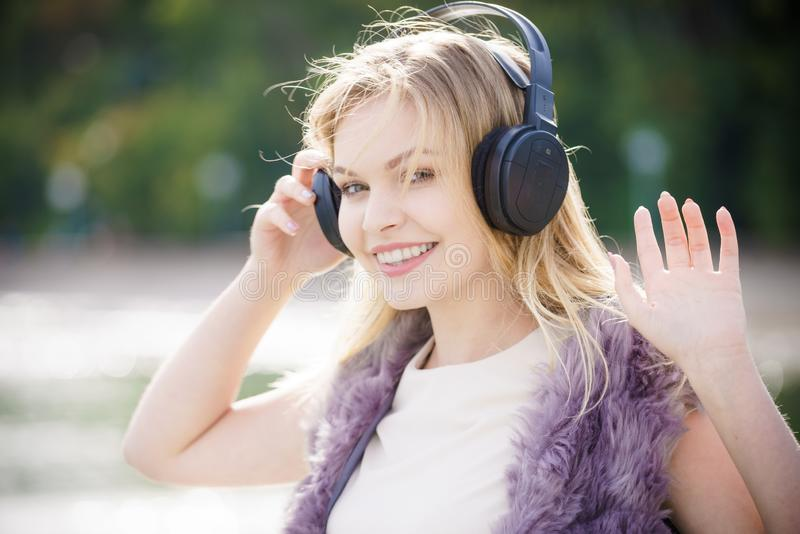 Happy woman wearing headphones outdoor. Happy joyful woman listening to music while being outdoor. Teenage female wearing headphones having fun on a walk stock photography