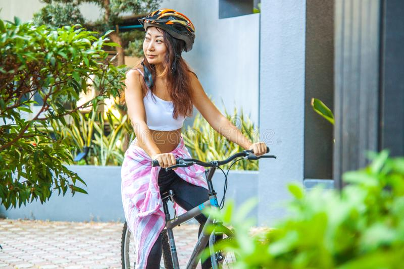 Happy woman wearing helmet riding bicycle in the summer. stock images