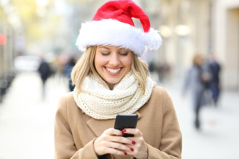 Woman reading phone text on christmas. Happy woman wearing santa hat reading phone text on christmas in the street royalty free stock images