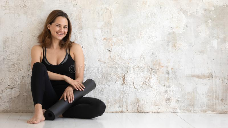 Happy smiling woman holding black yoga mat, sitting on floor royalty free stock photography