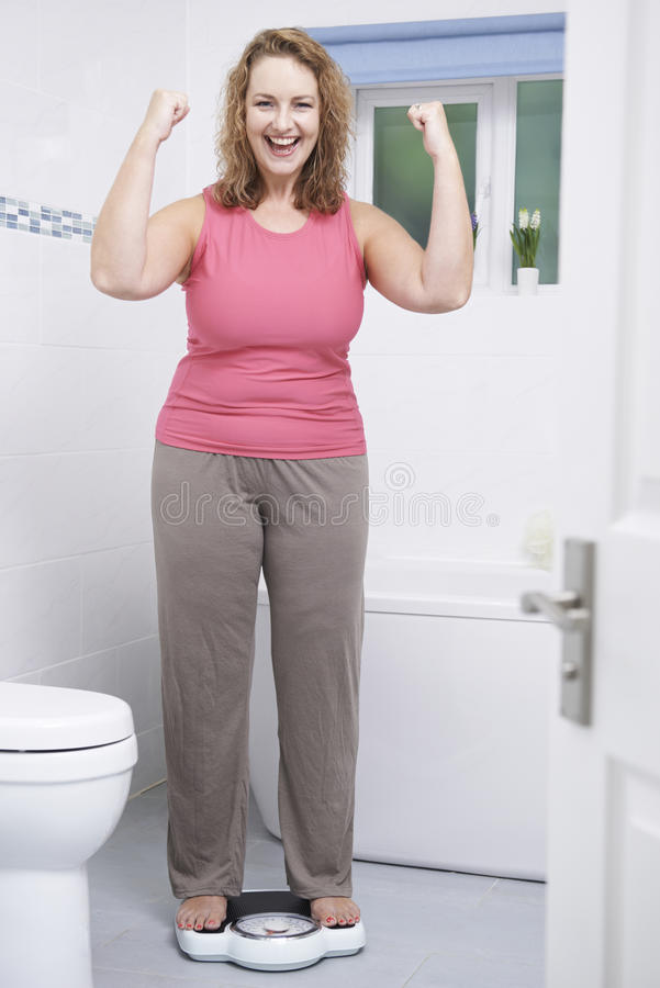 Happy Woman Weighing Herself On Scales In Bathroom royalty free stock photo