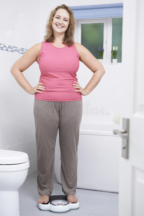 Happy Woman Weighing Herself On Scales In Bathroom stock photography