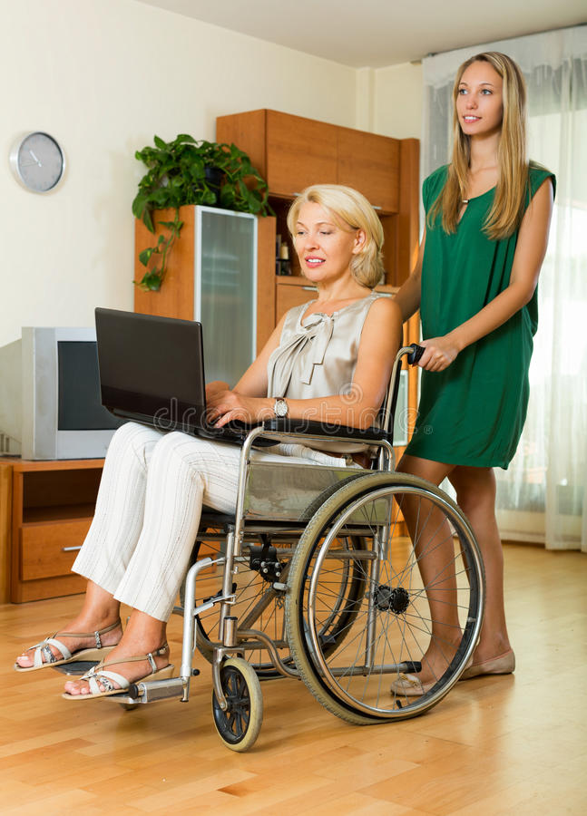 Happy woman in wheelchair working on laptop stock image