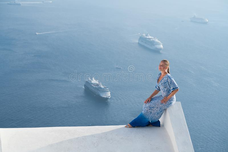 Happy woman in white and blue dress enjoying her holidays on Santorini, Greece. View on Caldera and Aegean sea from stock images