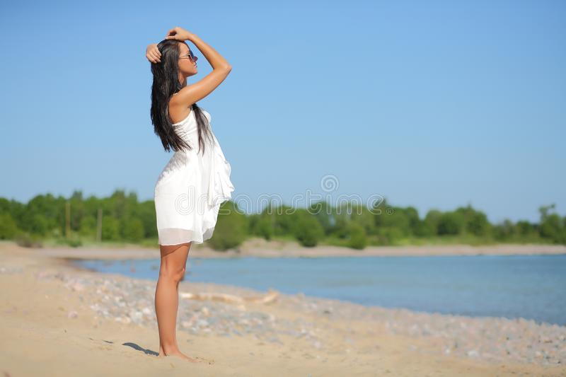 Happy woman in white dress on the beach. Young happy woman in white dress on the beach stock photos