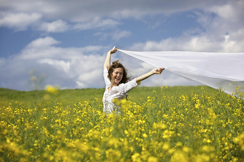 Happy woman with white piece of cloth in wind