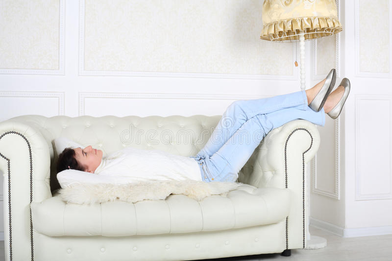 Happy woman in white sweater and jeans lies on sofa. At home and looks up royalty free stock images