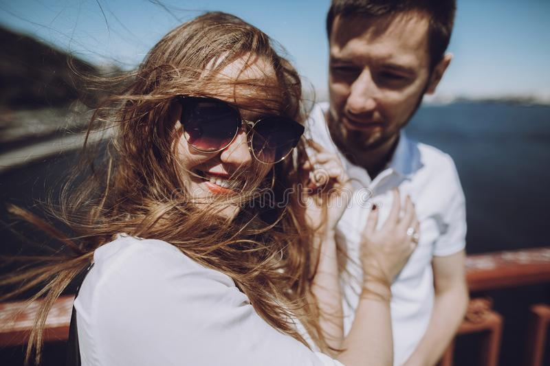 happy woman with windy hair in sunglasses smiling, stylish couple in love having fun on bridge in the summer city. modern woman royalty free stock photography