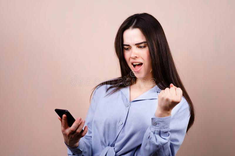 Happy woman winning online. Young excited lady using smart phone. Achievement, celebration, success concept royalty free stock photography